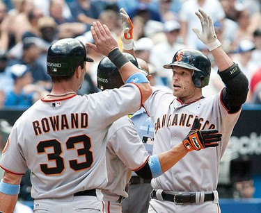 San Francisco Giants Freddy Sanchez (R) is congratulated by team mates after hitting a three-run home run off Toronto Blue Jays pitcher Brian Tallet in the sixth inning of their MLB interleague baseball game in Toronto June 20, 2010.   (REUTERS)