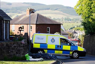 The body of a shooting victim lies covered with sheets in the village of Egremont in Cumbria, north east England June 2, 2010. A gunman killed at least 12 people in a rampage through quiet towns in and around the scenic Lake District of northwest England on Wednesday in Britain's worst shooting spree for 14 years. Terrified locals and walkers were told to stay indoors as 52-year-old taxi driver Derrick Bird opened fire on people in towns across the predominantly rural and sparsely populated county of Cumbria, one of Britain's top tourist destinations. In addition to the 12 dead, 25 others were wounded, including three whose condition was said to be critical, in shootings in 30 separate locations.  (REUTERS)