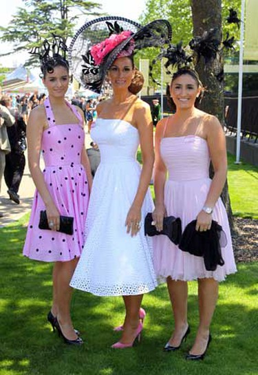 Isabell Kristensen (c) and racegoers pose for a photograph at Royal Ascot in southern England June 17, 2010. The event is known for attracting wild and often large head pieces.  (WENN.com)