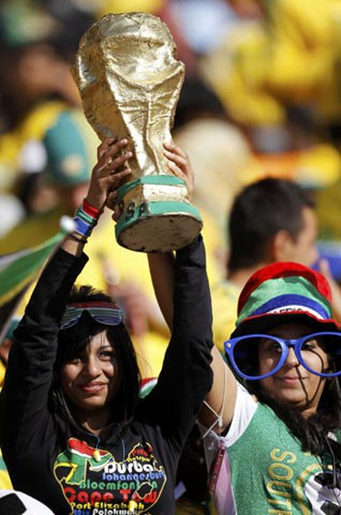 Soccer fans raise a replica of the World Cup trophy during the opening ceremony of the 2010 World Cup at Soccer City stadium in Johannesburg June 11, 2010. (Kai Pfaffenbach/REUTERS)