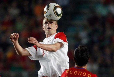 Poland's Nowak (L) heads the ball next to Spain's Xabi Alonso during a friendly soccer match in Murcia June 8, 2010. (REUTERS)