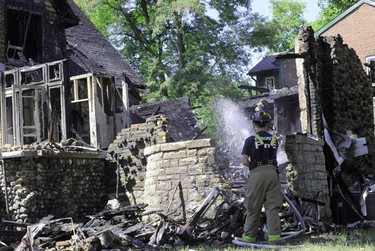 A Toronto Firefighter douses a smouldering old stone home on Indian Rd. after an early morning fire and explosion that rocked a west end neighbourhood.  (CHRIS DOUCETTE/Toronto Sun)