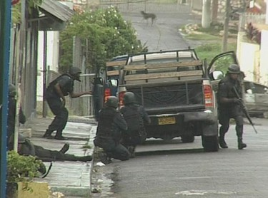 Riot police take to the streets in West Kingston, Jamaica, in this video grab taken May 23, 2010. Jamaica declared a state of emergency in two parishes of its capital Kingston on Sunday after shooting and firebomb attacks on police stations by suspected supporters of an alleged drug lord who faces extradition to the United States. (REUTERS)