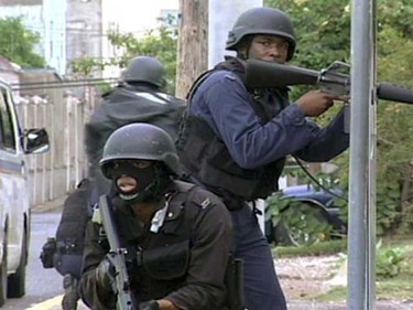 """Armed police officers patrol a street in Kingston, in this May 24, 2010 frame grab. Heavily armed police patrolled the Jamaican capital on Monday after at least three people were killed in an outbreak of violence by suspected supporters of an alleged drug lord who faces extradition to the United States. The government declared a state of emergency in sections of the capital Kingston and St. Andrew on Sunday, as Prime Minister Bruce Golding vowed """"strong and decisive action"""" to restore order.     (REUTERS)"""