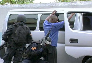 """Police officers search a man outside his van in Kingston, in this May 24, 2010 frame grab. Heavily armed police patrolled the Jamaican capital on Monday after at least three people were killed in an outbreak of violence by suspected supporters of an alleged drug lord who faces extradition to the United States. The government declared a state of emergency in sections of the capital Kingston and St. Andrew on Sunday, as Prime Minister Bruce Golding vowed """"strong and decisive action"""" to restore order.     (REUTERS)"""
