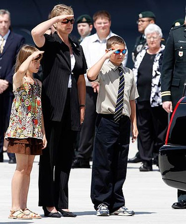 MJ, the wife of fallen Canadian soldier Colonel Geoff Parker, and their two children, Charlie (R) and Alexandria (L), salute the casket inside the hearse during a repatriation ceremony at Canadian Forces Base Trenton May 21, 2010. Colonel Parker was killed while travelling in a NATO convoy when an explosive device was detonated near their vehicles on May 18 in Afghanistan.  (REUTERS)