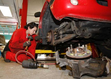 Licensed mechanic Maud Sailland, originally from Bordeaux, France, takes the tire off to pick-up truck to replace a spindle. (Jack Boland/Toronto Sun)