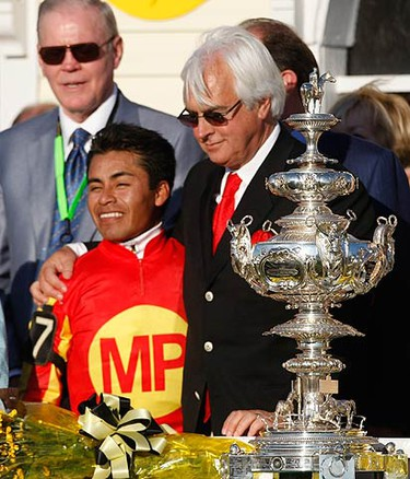 Trainer Bob Baffert (R) and jockey Martin Garcia (L) celebrate in front of the Woodlawn Vase after winning the 135th Preakness horse race with their horse Lookin At Lucky at Pimlico race track in Baltimore, Maryland May 15, 2010.   (REUTERS)