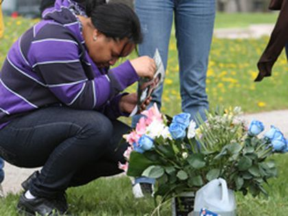 Amanda Manon kneels beside the spot where her brother, Junior, died.  Amanda along with friends and family brought flowers and candles to the site. (CRAIG ROBERTSON/Toronto Sun)