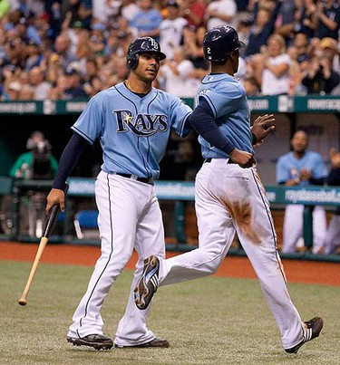 Tampa Bay Rays' B.J. Upton (R) celebrates with the Rays' Carlos Pena after scoring against the Toronto Blue Jays during the fifth inning of their MLB American League baseball game in St. Petersburg, Florida on April 25, 2010, in St. Petersburg, Fla. (REUTERS)