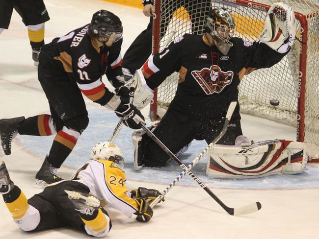 Brandon Wheat Kings' Jay Fehr makes a point blank shot on Calgary Hitmen goalie Martin Jones as defenceman Zak Stebner closes in during the first period in Game 4 of the Eastern Conference Final Wednesday in Brandon. COLIN CORNEAU/BRANDON SUN