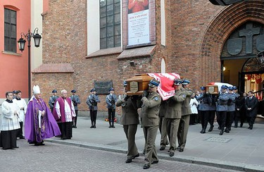Soldiers carry coffins of late Polish President Lech Kaczynski (front) and his wife Maria during a short mass inside the Cathedral of St. John in Warsaw, on April 18, 2010. Polish and foreign leaders attended a funeral mass on Sunday for President Lech Kaczynski and his wife Maria, but a volcanic ash cloud over Europe prevented some overseas guests from joining them.  (REUTERS)