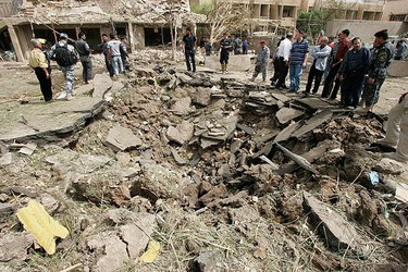 Policemen and residents gather around the damage made by a bomb attack near the Egyptian Embassy in Baghdad's Mansour district on April 4, 2010. Suicide attackers detonated car bombs near three embassies in Baghdad on Sunday, killing at least 32 people and wounding more than 100, authorities said. (REUTERS)
