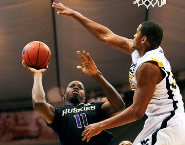 Washington's Matthew Bryan-Amaning (L) goes to the basket against West Virginia's Wellington Smith during the first half of their NCAA East Regional college basketball game in Syracuse, New York, on March 25, 2010. (REUTERS)
