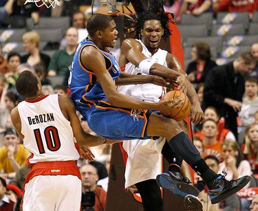 Oklahoma City Thunder forward Kevin Durant (C) is fouled while going to the basket between Toronto Raptors forwards DeMar DeRozan and Chris Bosh (R) during the first half of their NBA basketball game in Toronto on March 19, 2010. (REUTERS)