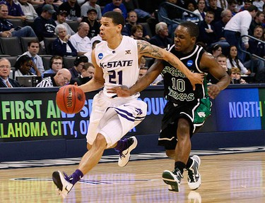 Kansas State guard Denis Clemente (21) holds back North Texas guard Josh White (10) in the second half of their NCAA Division I Men's Basketball Tournament game in Oklahoma City, Oklahoma, on March 18, 2010. (REUTERS)
