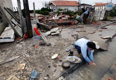 A resident of Yves, near La Rochelle, cleans plates in a flooded street in front of her destroyed house March 1, 2010 after severe storms swept western France. France's government has declared a natural disaster, enabling victims to claim compensation and free up insurance claims. France will also seek European Union aid for the region. (REGIS DUVIGNAU/Reuters)