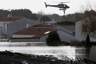 A resident of La-Faute-sur-Mer is rescued from floods by a helicopter after severe storms swept western France February 28, 2010. (STEPHANE MAHE/Reuters)