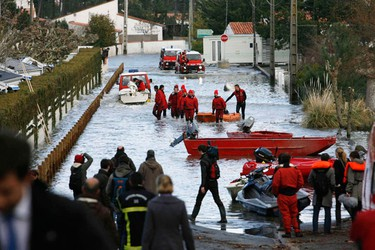 Rescue personnel work at a flooded street in La-Faute-sur-Mer in western France March 1, 2010. President Nicolas Sarkozy promised on Monday to investigate how sea levees broke during heavy storms at the weekend, unleashing floods that killed at least 51 people. The government has declared a natural disaster, which will enable victims to claim compensation and free up insurance flooding claims and it has also announced it will seek European Union aid for the region. (STEPHANE MAHE/Reuters)