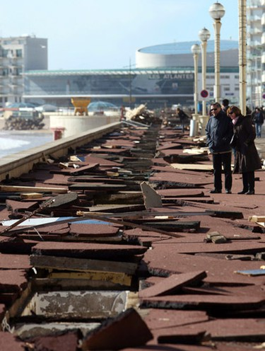 People look on at the damage caused to the boardwalk on the seafront at Les Sables d'Olonne, in western France following a major storm which caused flooding and destruction throughout much of France early February 28, 2010. (STEPHANE MAHE/Reuters)