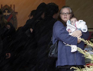 A woman holds baby Kendra Einboden at the funeral for Ken Einboden, 44, and his daughter Britney, 12, at the United Church on March 13, 2010. It's believed a kitchen fire led to the blaze that killed Einboden and his daughter. (DAVE ABEL, Toronto Sun)
