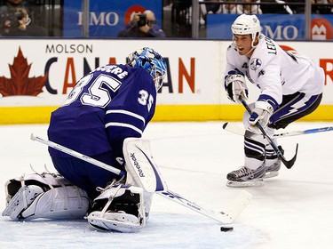 Toronto Maple Leafs goalie Jean-Sebastien Giguere makes a save on a shot by Tampa Bay Lightning forward Vincent Lecavalier (L) during the first period of their NHL hockey game in Toronto on March 11, 2010. (REUTERS)