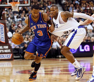 New York Knicks forward Tracy McGrady drives past Toronto Raptors forward Sonny Weems (R) during the first half of their NBA basketball game in Toronto on March 5, 2010.  (REUTERS)