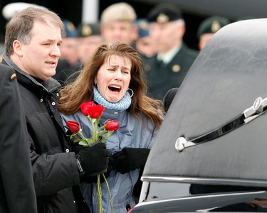 Family members carry roses to the hearse carrying the casket of Canadian soldier Corporal Joshua Caleb Baker during a repatriation ceremony at Canadian Forces Base Trenton February 15, 2010. Corporal Baker of the Loyal Edmonton Regiment was killed and four others were injured in a training accident on a range located approximately 4 km (2.5 miles) northeast of Kandahar City, Afghanistan on February 12.   (REUTERS)