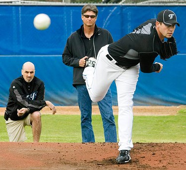 Toronto Blue Jays pitcher Dustin McGowan throws at the team's MLB baseball spring training facility as minor league pitching coach Dane Johnson (C) and trainer George Poulis (L) look on at the team's training facility in Dunedin, Florida on Feb. 20, 2010. (REUTERS)