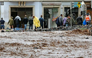 People walk along a flooded street in downtown Funchal, Madeira on Feb. 20, 2010. Heavy rain caused flash floods all around the Portuguese island and the local government has confirmed 32 dead. (REUTERS)