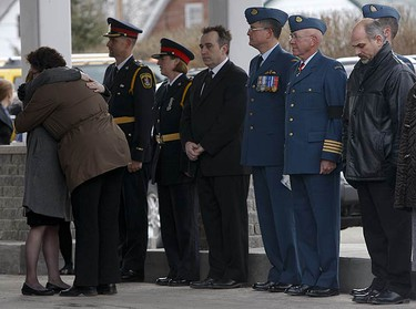 Two women hug outside the funeral home in front of Belleville Police Chief Cory McMullan, Belleville Mayor Neil Ellis (in tie) interim Lieut.-Col. Dave Murphy of CFB Trenton 8 and Hon. Col. Glenn Rainbird. (JACK BOLAND, Toronto Sun)