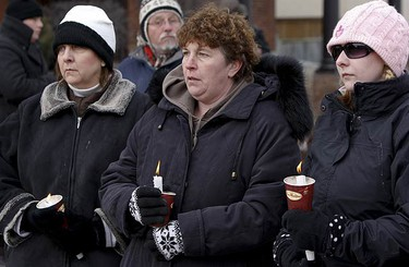 A trio of women stand with makeshift candle holders across the street from the funeral home. (JACK BOLAND, Toronto Sun)