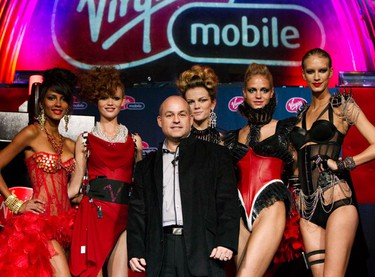 Lingerie models pose with Robert Blumenthal, president of Virgin Mobile Canada, after a fashion show to promote their new HSPA+ cell phone network in Toronto, February 2, 2010.   (REUTERS)