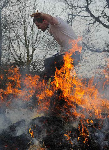 A competitor runs through a burning field during the Tough Guy event in Perton, central England, on Jan. 31, 2010. The annual event to raise cash for charity challenges thousands of international competitors in a cross country run followed by an assault course consisting of 21 obstacles including water, fire and tunnels.  (REUTERS)