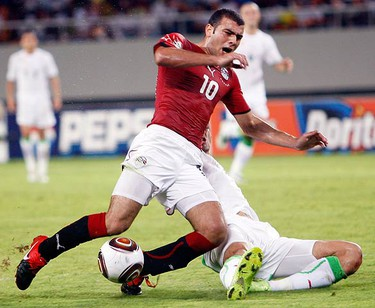 Emad Moteab of Egypt challenges Rafik Halliche of Algeria during their African Nations Cup semi-final soccer match at Ombaka stadium in Benguela on Jan. 28, 2010. (REUTERS)
