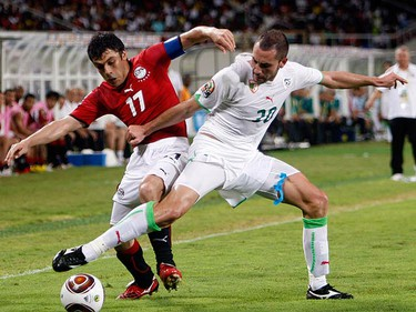 Ahmed Hassan of Egypt challenges Meghni Mourad of Algeria during their African Nations Cup semi-final soccer match at Ombaka stadium in Benguela on Jan. 28, 2010. (REUTERS)