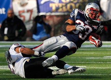 New England Patriots running back Kevin Faulk (R) is tackled by Baltimore Ravens cornerback Chris Carr (L) in the second quarter of their NFL AFC wild-card playoff football game in Foxborough, Massachusetts on Jan. 10, 2010. (REUTERS)
