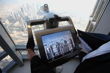 A member of the media looks through electronic binoculars set up at the observation deck on the 124th floor of the Burj Khalifa Tower, the world's tallest tower, in Dubai Jan. 4, 2010. REUTERS/Ahmed Jadallah
