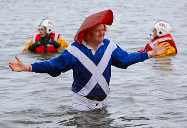 A man gestures as he walks out of the freezing water in the Firth of Forth during the annual 'Looney Dook' charity New Year's Day swim in South Queensferry near Edinburgh, Scotland January 1, 2010.   (REUTERS)