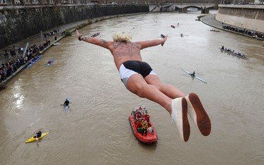 Giuseppe Palmulli of Italy dives into the Tiber River as part of traditional New Year celebrations from one of Rome's many bridges January 1, 2010. Some four men sprinkled the muddy water of the Tiber with sparkling wine before taking the plunge from the Cavour bridge, continuing an annual tradition which dates back to 1946. (REUTERS)