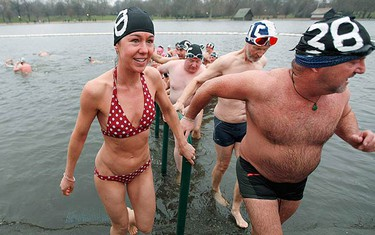 """Swimmers leave the water after a swim in the Serpentine river on Christmas Day in Hyde Park, central London, on Dec. 25, 2009. For over 100 years swimmers have taken part in the Christmas Day """"Peter Pan"""" swim in the Serpentine. (REUTERS)"""