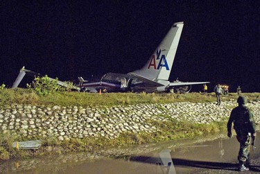 Officials examine the wreckage of American Airlines flight AA331, which crashed upon landing at Kingston's Norman Manley International Airport, late December 22, 2009. The American Airlines Boeing 737 overshot the runway while landing in driving rain at the international airport in Kingston, Jamaica on Tuesday night, but the company said there were no fatalities or serious injuries. The Jamaica Observer newspaper reported 40 injured passengers but did not give details about their condition. CNN said four of the passengers were in serious condition.      REUTERS/Andrew P. Smith