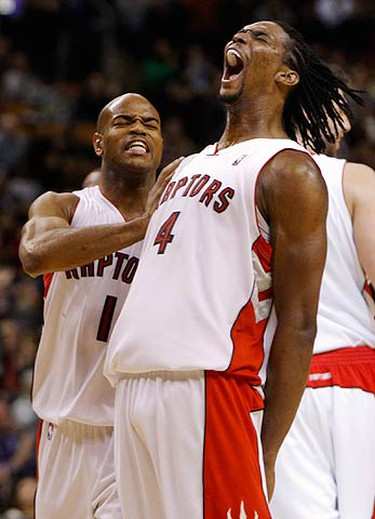 Toronto Raptors Chris Bosh celebrates his basket with teammate Jarrett Jack (L) during the second half of their NBA basketball game against the New Orleans Hornets in Toronto on Dec. 20, 2009. (REUTERS)