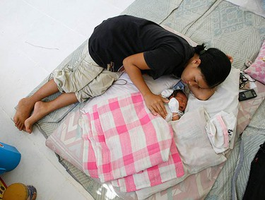 A mother stays beside her five-day-old baby in a Spanish government AEICD evacuation centre after they were forcefully evacuated from the Mayon volcano slopes in Guinobatan, Albay, 500 km (310 miles) south of Manila on Dec. 18, 2009 in Legazpi city, Albay province, about 500 kilometers (300 miles) southeast of Manila, Philippines. More than 34, 000 people living around the volcano have been evacuated following increased restiveness of the country's most active volcano. (REUTERS)