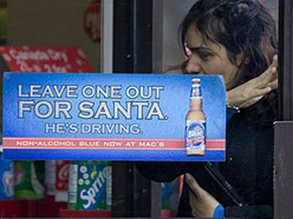 A woman walks into a Mac's store at Gerrard and Mutual Sts. yesterday. A new ad campaign for de-alcoholized beer has Torontonians saying it's not an appropriate message for children. (Greg Henkenhaf, Toronto Sun)