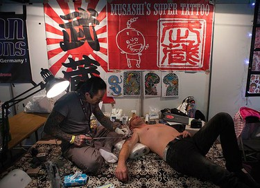 A tattoo artist works at the Berlin International Tattoo convention in Berlin, on Dec. 4, 2009. Some 180 international tattoo, piercing and body artists took part in the event. (REUTERS)