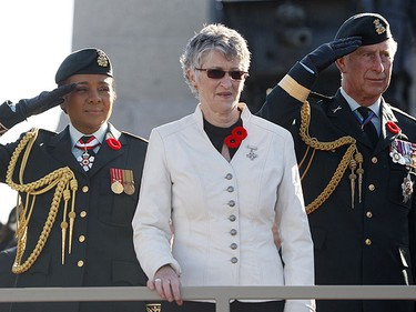 Canada's Governor General Michaelle Jean (L) and Britain's Prince Charles (R) salute veterans while standing with Silver Cross Mother Della Morley during Remembrance Day ceremonies at the National War Memorial in Ottawa Nov. 11, 2009.       REUTERS/Chris Wattie