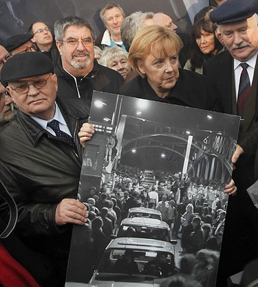 German Chancellor Angela Merkel (C), former Soviet Union President Mikhail Gorbachev (L) and former Polish President Lech Walesa pose with a historical picture showing Bornholmer Bridge (Bornholmer Bruecke) in Berlin Nov. 9, 2009, during celebrations to mark the 20th anniversary of the fall of the Berlin Wall.         REUTERS/Tobias Schwarz