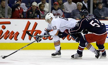 Edmonton Oilers' Ales Hemsky (L) and Columbus Blue Jackets' Fedor Tyutin, of Russia, chase a a loose puck during the first period of an NHL hockey game in Columbus, Ohio, on Nov. 16, 2009. (REUTERS)