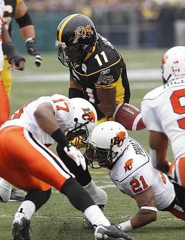 Hamilton Tiger-Cats' James Drisan looses the ball as he attampts to drive five yards for a touchdown in front of  BC Lions'  Darren Toney and Ryan Phillips  during first half CFL Eastern Semi-Final action between the Hamilton Tiger-Cats and the B.C. Lions at Ivor Wynne Stadium in Hamilton, on Nov. 15, 2009. (ALEX UROSEVIC, Sun Media)
